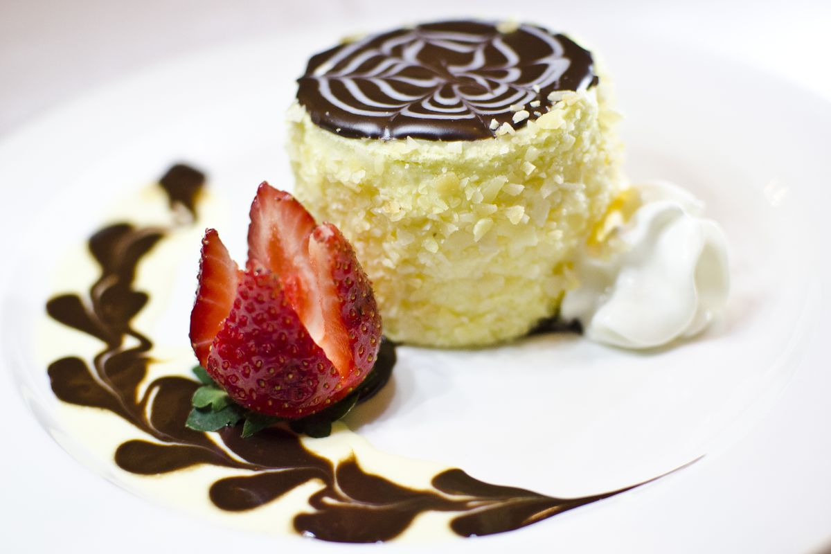 A small round piece of Boston cream pie sits on a white plate, garnished with a strawberry, chocolate sauce shaped like a row of hearts, and whipped cream