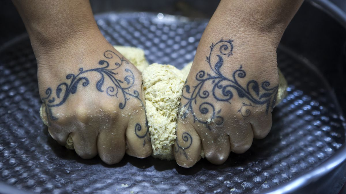 A pair of tattooed hands kneading dough