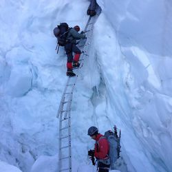 Climbing the Khumbu Ice Fall. David Roskelley is standing at the base of the ladder and Steve Pearson is taking the photo.