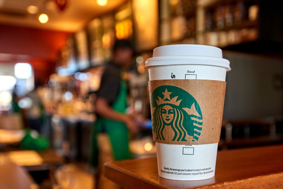 A paper cup with a Starbucks-branded cardboard sleeve sits on a wooden counter as obscured baristas work in the background of a Starbucks coffee shop.