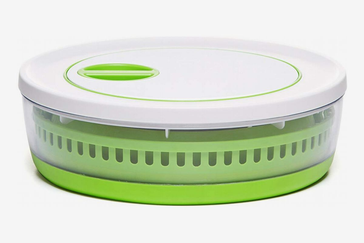 A green and white plastic salad spinner