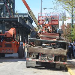 3:45 p.m. Equipment driving into the work site, as concession workers line up on the sidewalk across the street -