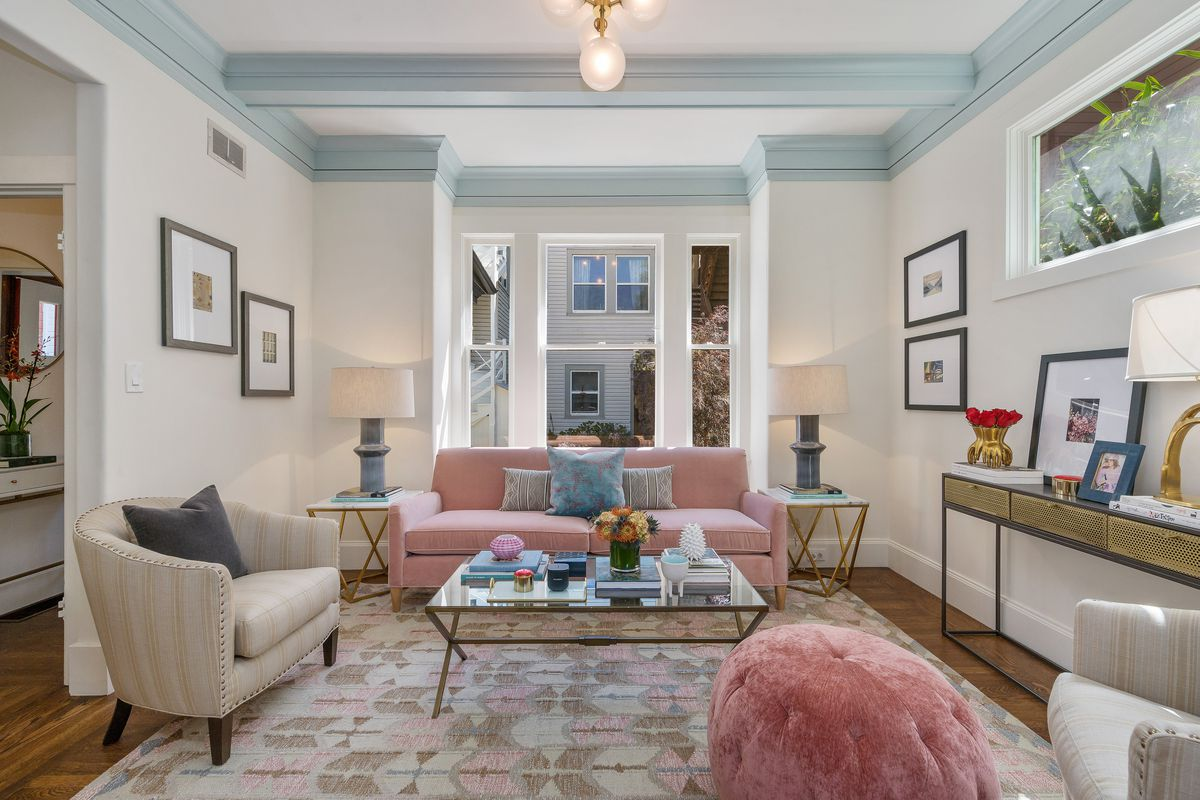 Room features white walls and ceiling trim painted baby blue. There's a sofa near the window, with lots of natural light, as well as two chairs and a rug.