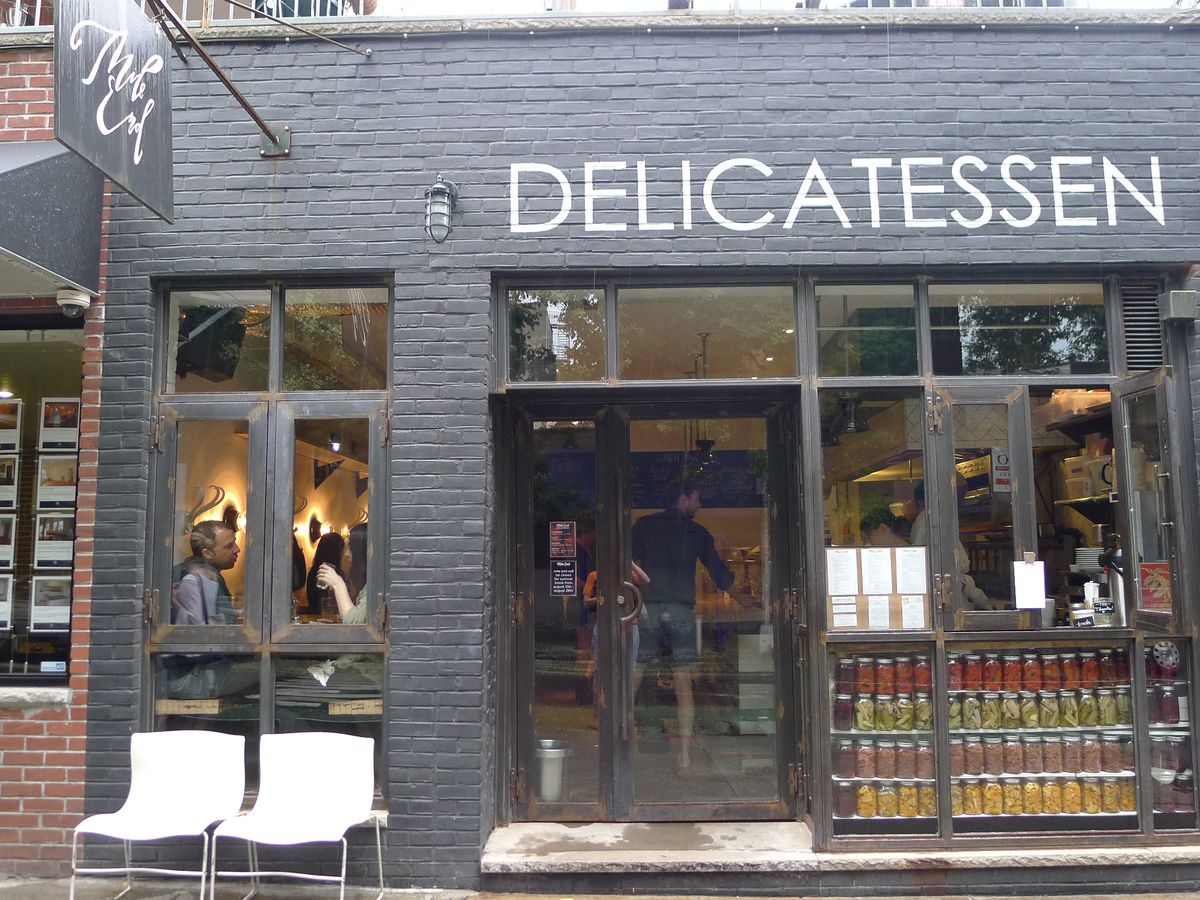 """A charcoal-colored building with the word """"DELICATESSEN"""" painted above its large windows."""