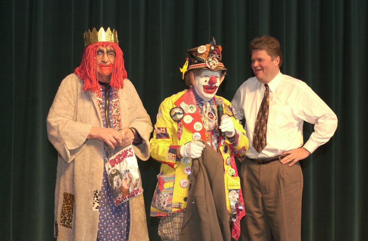 Three people standing together in front of a dark green curtain. The two left ones are dressed as clowns—one with a crown and red wig, the middle one with a yellow coat with red lapels and lots of buttons. Man on the right is in business casual.