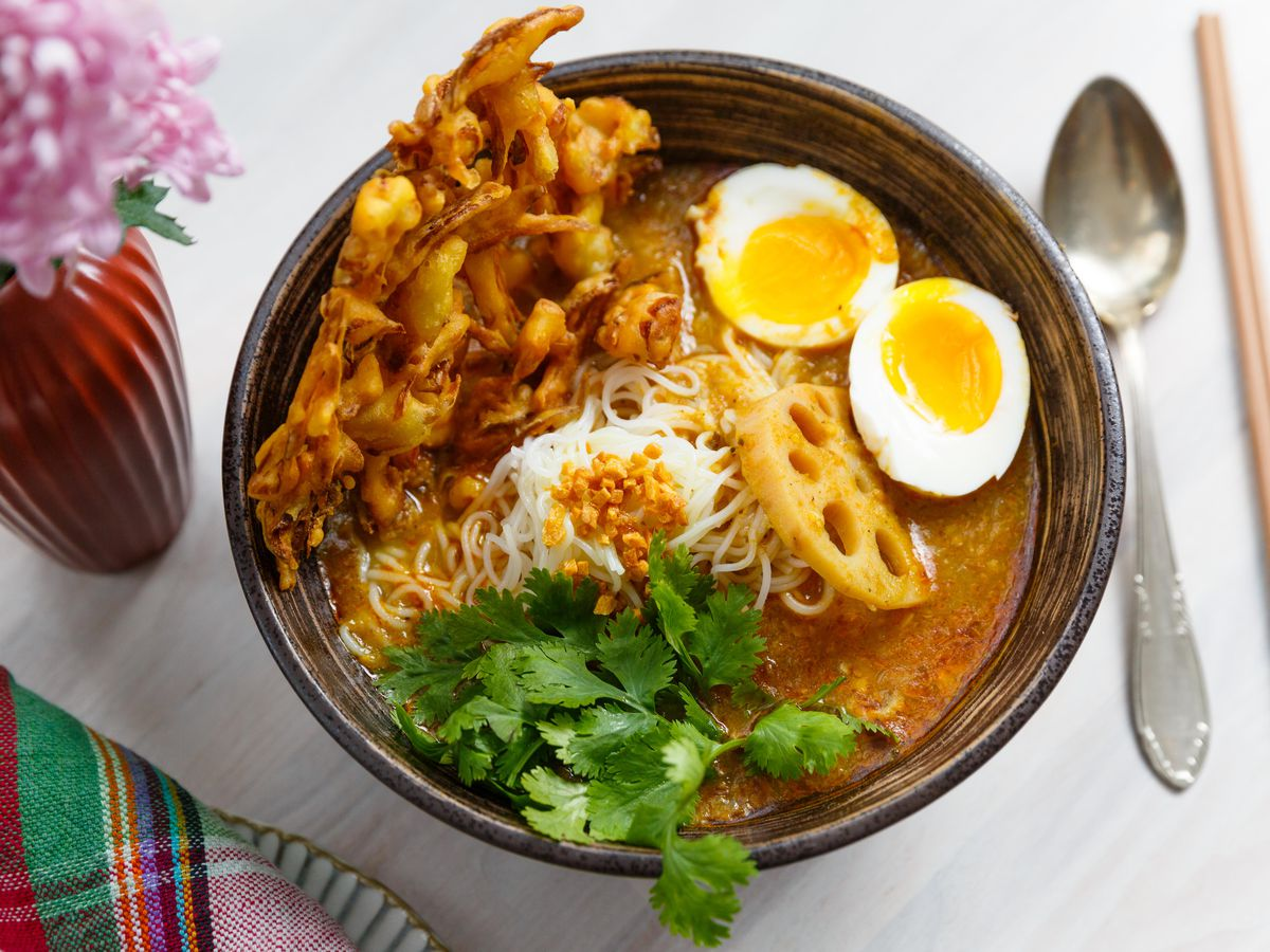 A bowl of soup with crispy shallots, two boiled eggs sliced in half, a pile of cilantro, all swimming in a red sauce