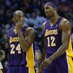 Los Angeles Lakers guard Kobe Bryant (24) and center Dwight Howard (12) walk off the court during a time out in the fourth quarter of an NBA basketball game against the Oklahoma City Thunder in Oklahoma City, Friday, Dec. 7, 2012. Oklahoma City won 114-108.(AP Photo/Sue Ogrocki)