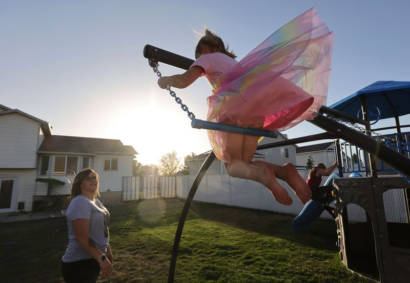 Stephanie Parkin watches daughter Riley, 5, swing at their home in Roy on Thursday, May 20, 2021. The Parkins say they severely limit screen use by their children.