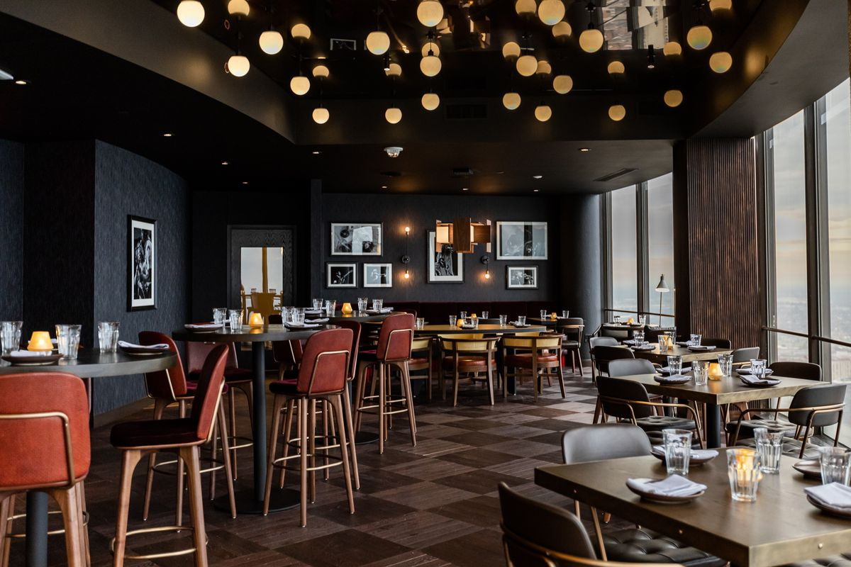 Globe lights hang from the ceiling like stars inside the Hearth 71 dining room at the Highlands next to curved windows looking out over the city.