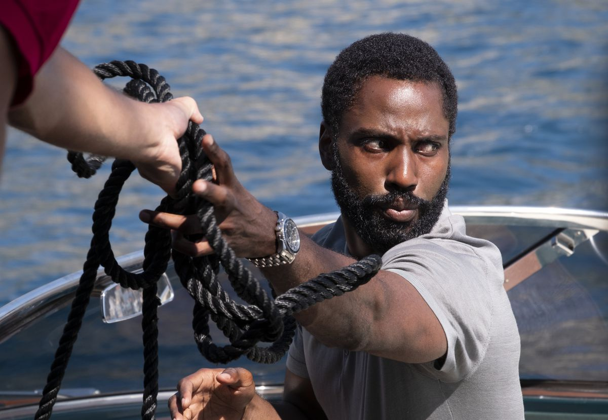 John David Washington stands on a boat, grabbing a thick black rope in Tenet