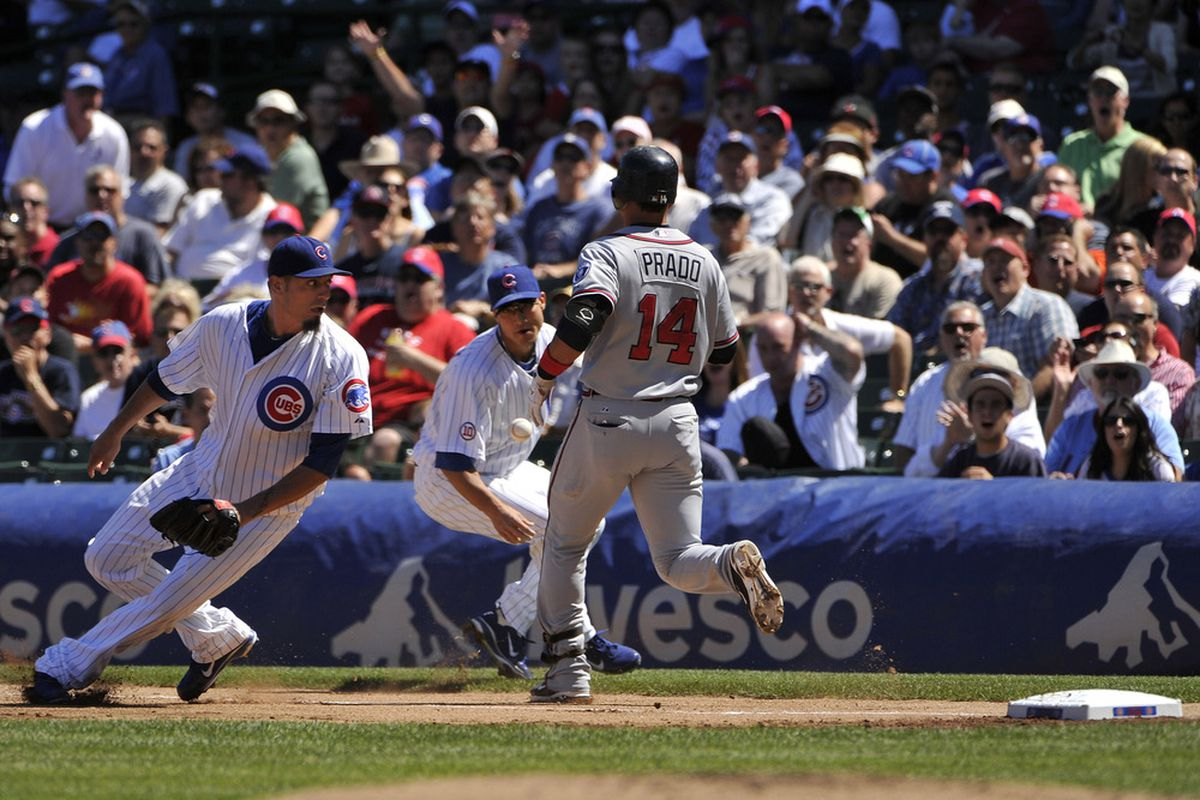Starting pitcher Matt Garza of the Chicago Cubs makes a fielding error on a ground ball hit by Martin Prado of the Atlanta Braves during the first inning at Wrigley Field in Chicago, Illinois.  (Photo by Brian Kersey/Getty Images)