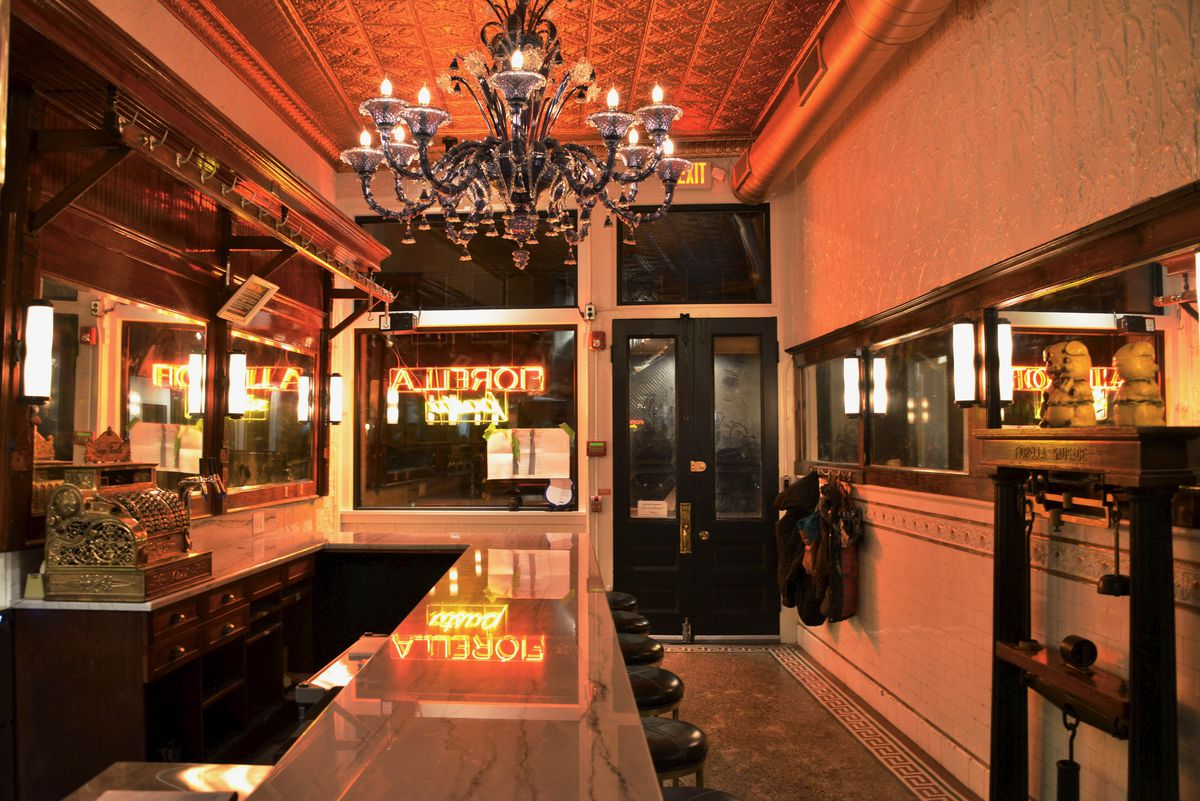 interior of restaurant with tin ceiling, marble bar top, and glowing chandelier