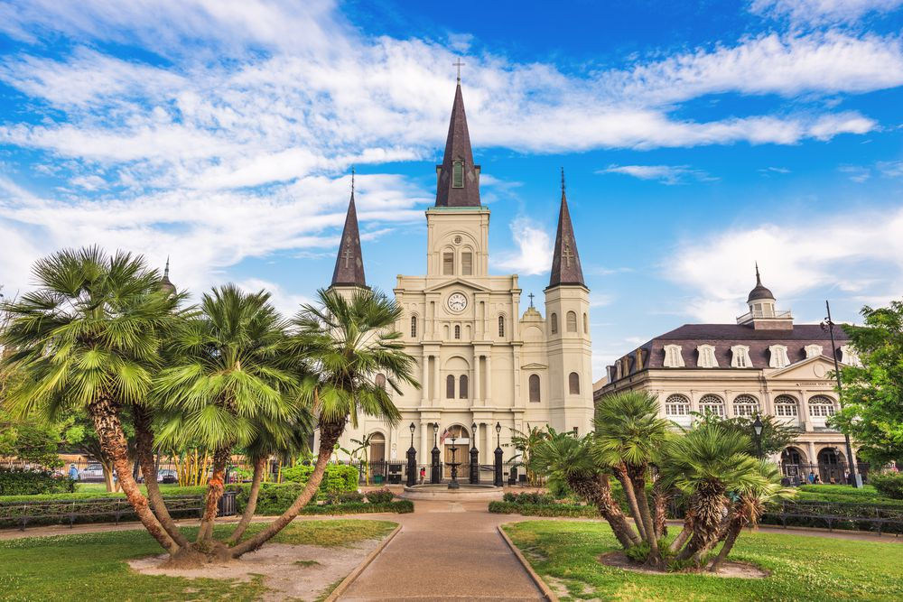 The exterior of the St. Louis Cathedral in New Orleans. The facade is tan with dark brown towers. There are palm trees and grass lining a red brick path leading to the cathedral.