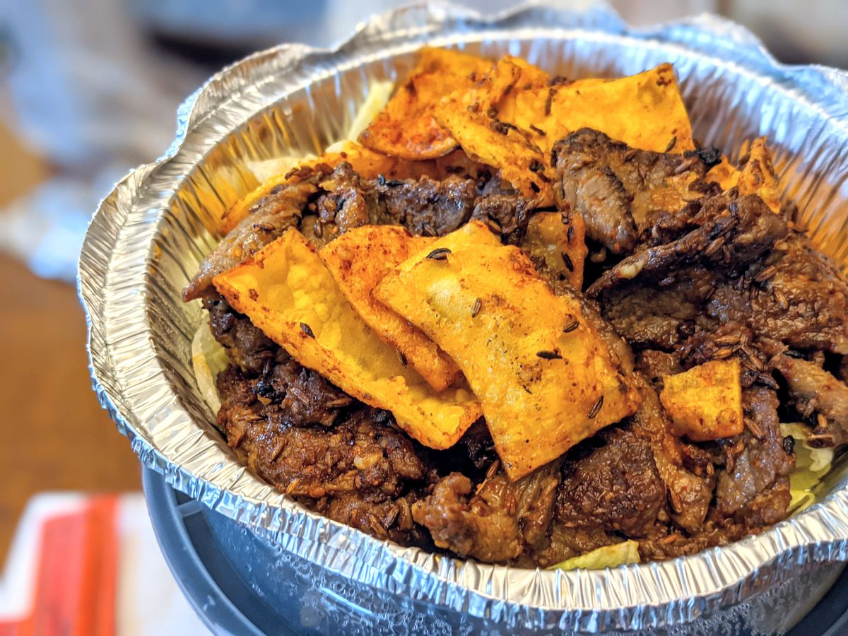 Round aluminum takeout container full of slices of beef with crispy wonton chips.