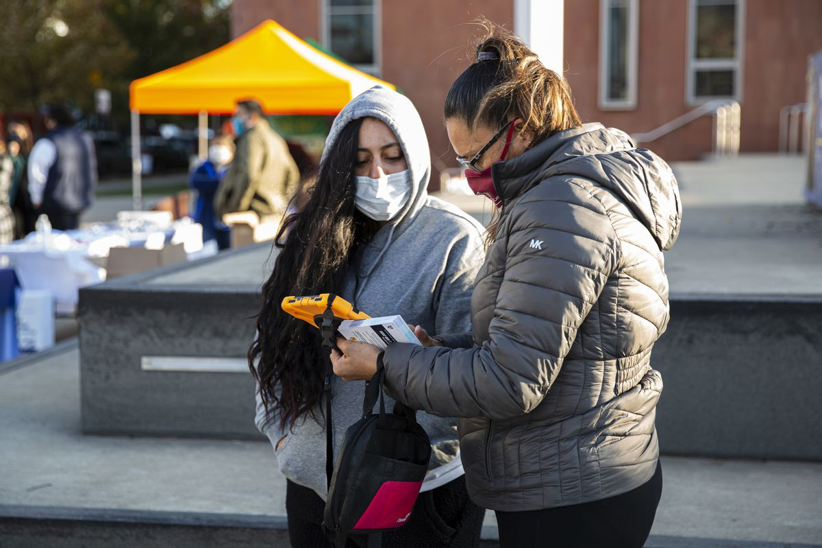 A woman has her information taken by a Census taker during a Census event at Back of the Yards College Prep H.S. at 2111 W. 47th St. in Back of Yards, Thursday, Oct. 15, 2020.
