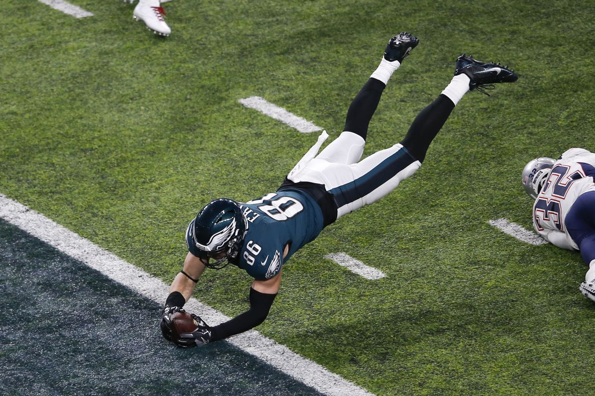 A Philadelphia Eagles football player scores a touchdown by leaping football-first into the end zone.