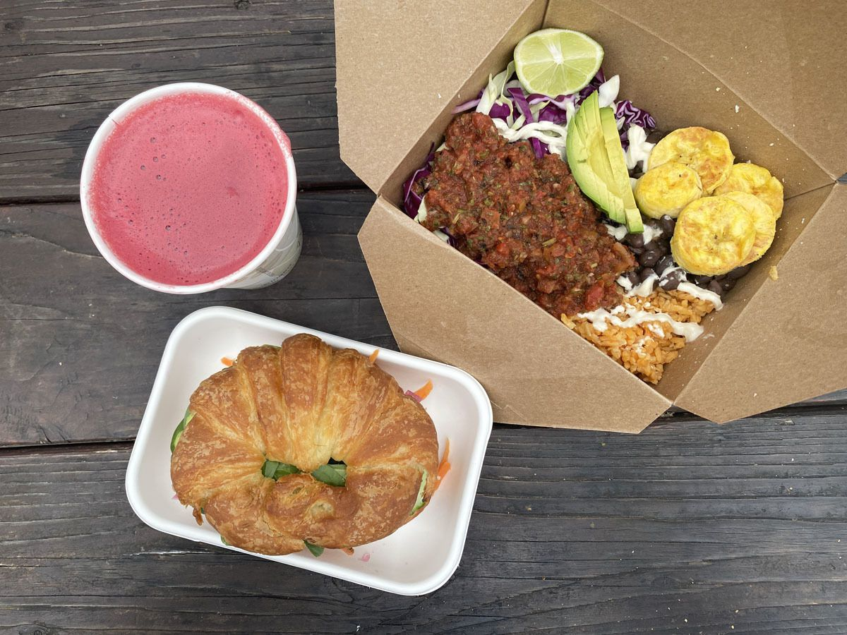 A photo of the croissant sandwich, rainbow rice bowl, and beet juice drink at Hue Vegan Cafe