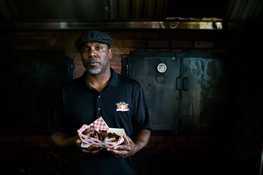 Bradrick Cooper owner of Coop's West Texas BBQ stands in front of his smoker holding a basket of smoked sausage