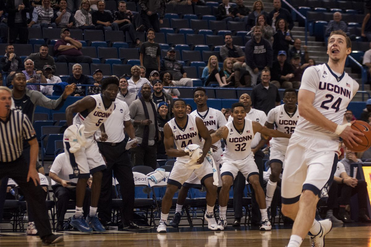 Walk-on Christian Foxen goes in for the dunk as his teammates watch excitedly.