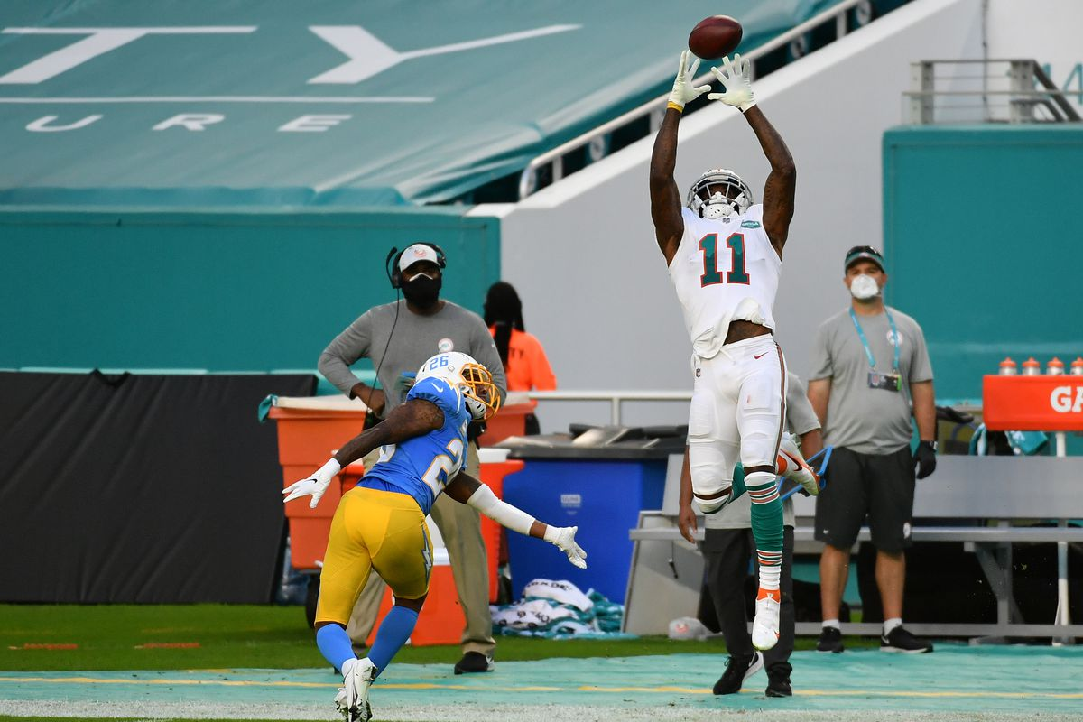 Miami Dolphins wide receiver DeVante Parker (11) makes a catch in front of Los Angeles Chargers cornerback Casey Hayward (26) during the first half at Hard Rock Stadium.