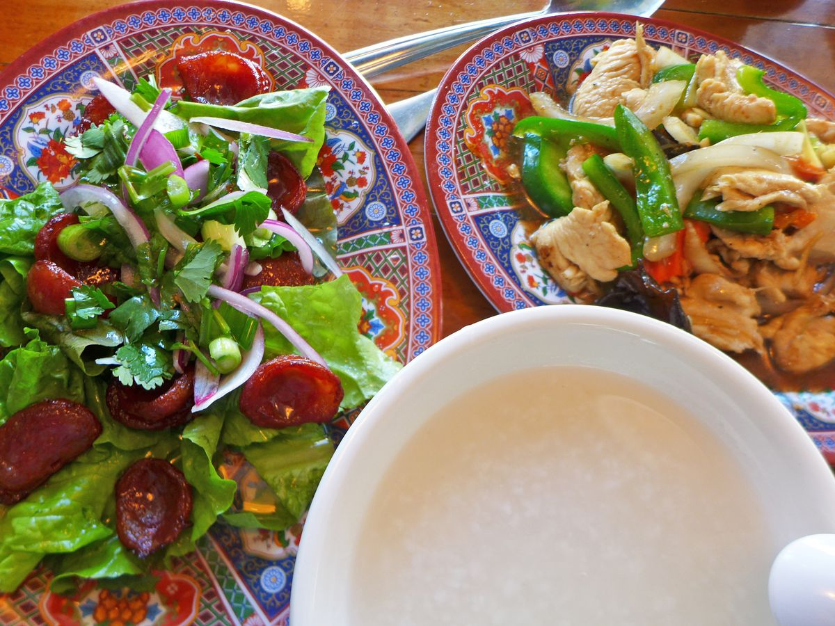 In the foreground a bowl of white rice soup flanked by two bigger and more colorful side dishes.