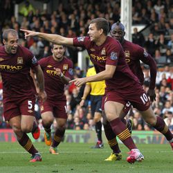 Manchester City's Edin Dzeko, center, celebrates his goal against Fulham with teammates during their English Premier League soccer match at Craven Cottage, London, Saturday, Sept. 29, 2012.