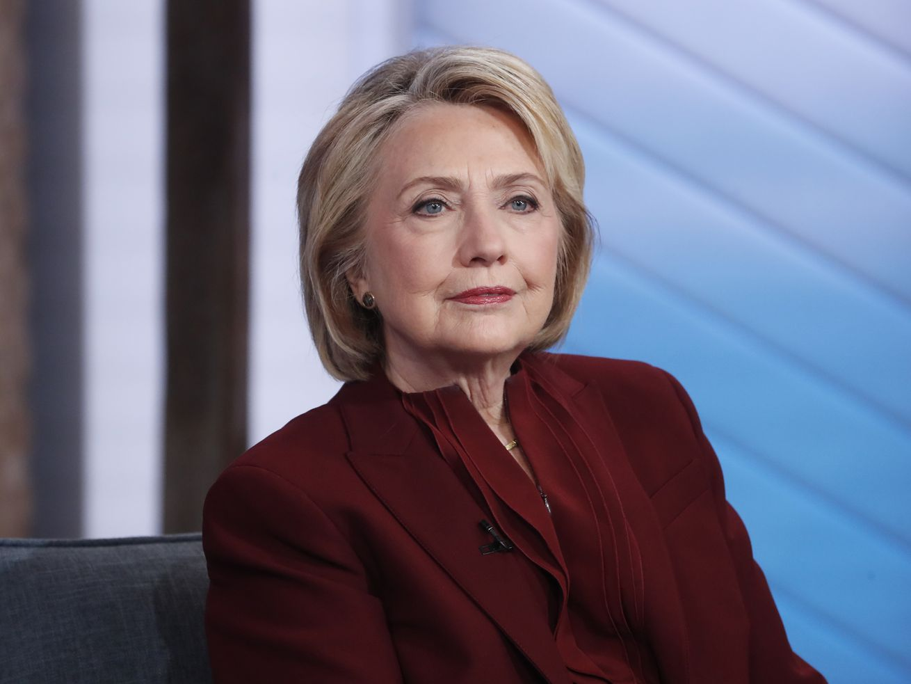 In a dark red suit, Clinton smiles slightly, sitting in a blue studio.