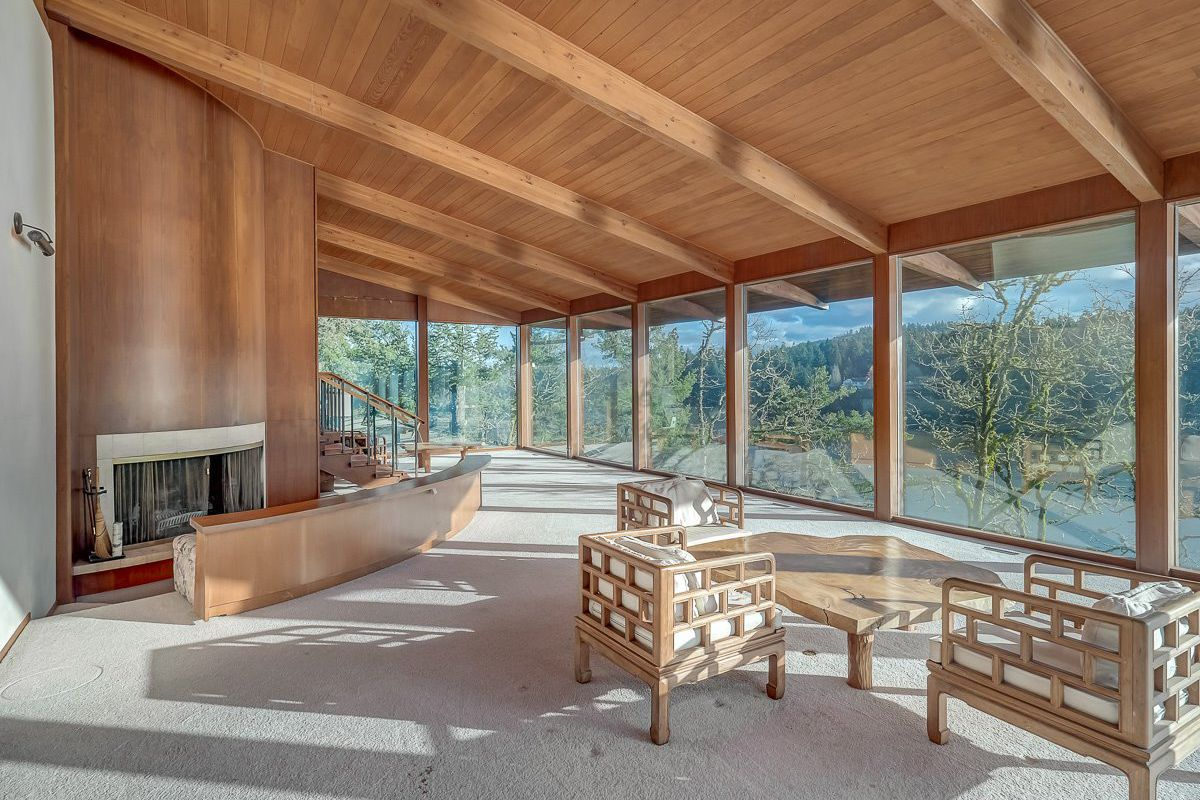 Interior of great room with sloping, beamed ceilings, a wall of windows overlooking a lake, and open-plan space with curved fireplace and built-in couch placed in sunken seating area.