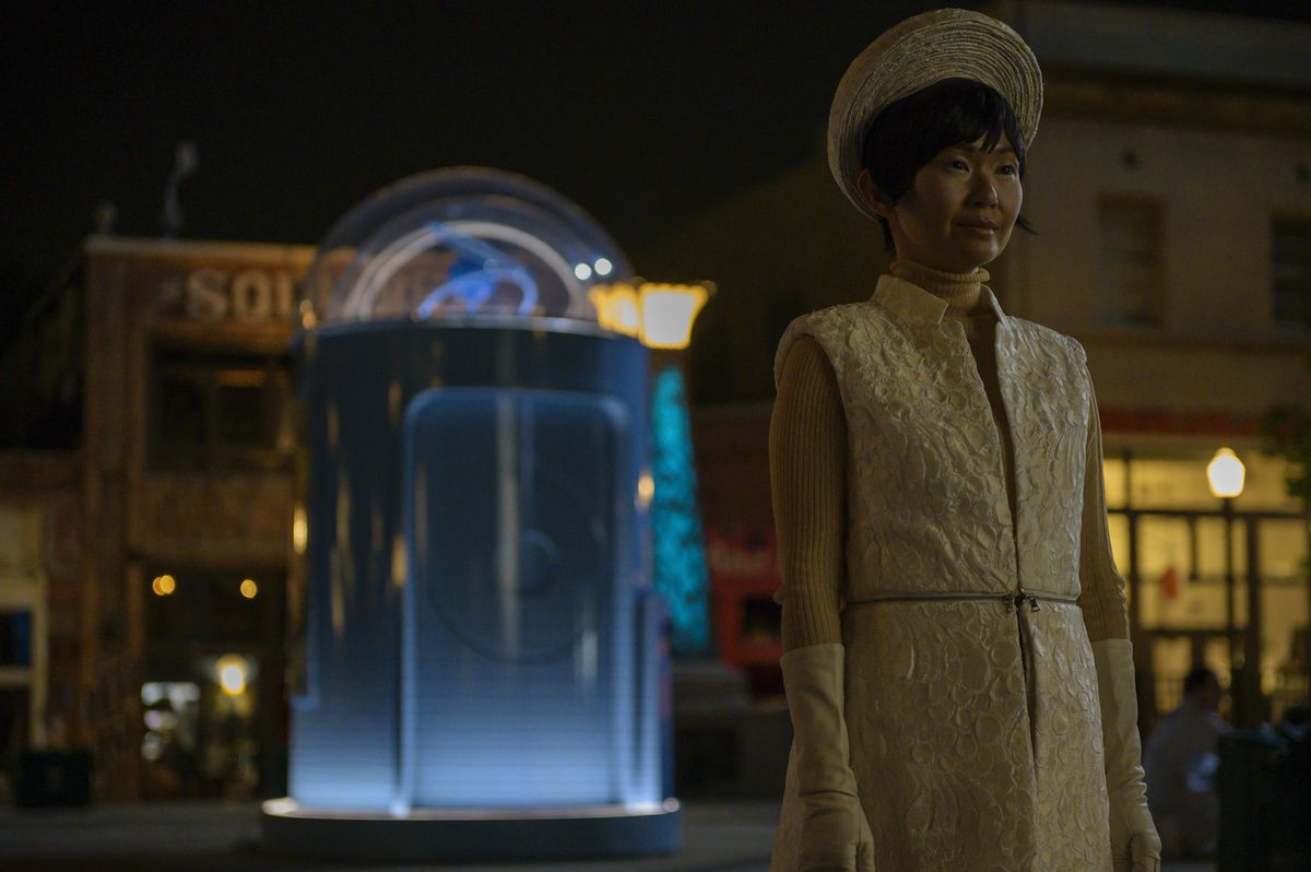 lady triu stands in front of a doctor manhattan phone booth in a white dress and hat