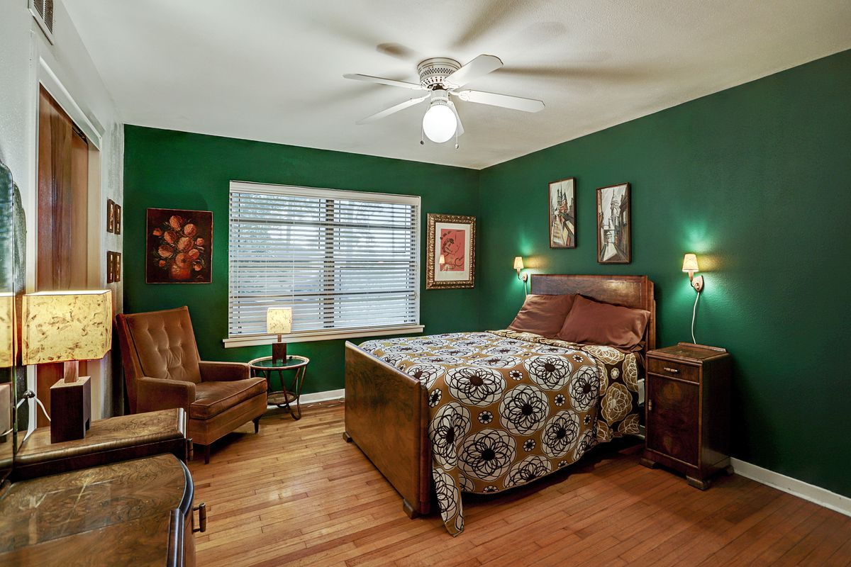 A bedroom has wood floors, a flower-pattern bed, and green accent walls.
