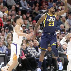 Utah Jazz forward Royce O'Neale (23) misses the ball after Phoenix Suns guard Devin Booker (1) tipped it away during an NBA game at the Vivint Smart Home Arena in Salt Lake City on Monday, Feb. 24, 2020.