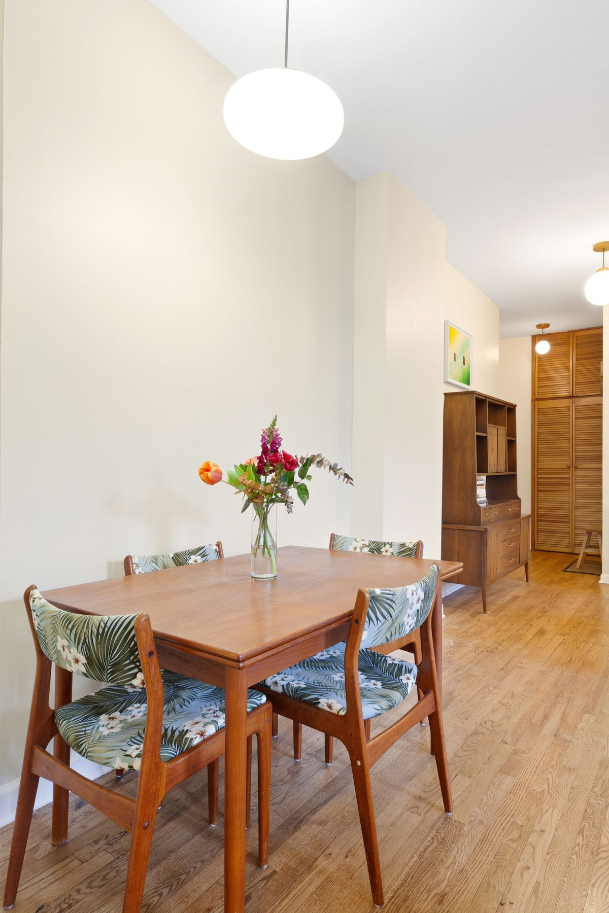 A dining area with a small table, four chairs, beige walls, and hardwood floors.