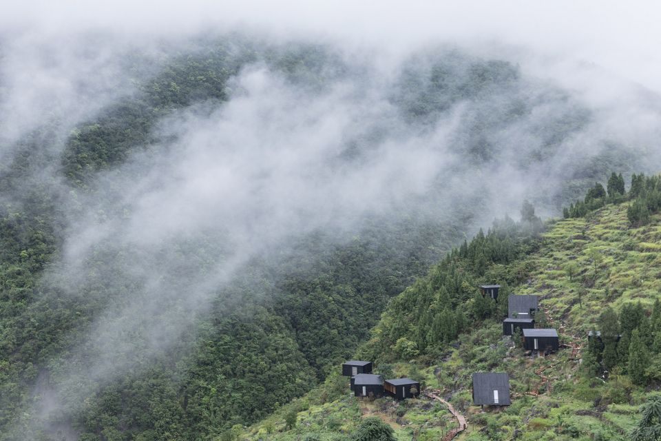 A group of cabins with charred wood facades on the side of a mountain. Below the vista are clouds and valleys full of trees.