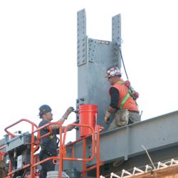 Steel workers securing a piece in the left-field bleachers -
