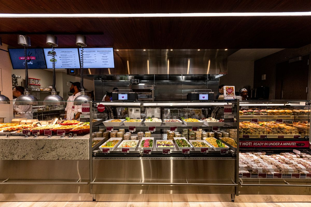 the deli counter cases at Plum Market with rows of sandwiches, chicken pot pies, salads, and more
