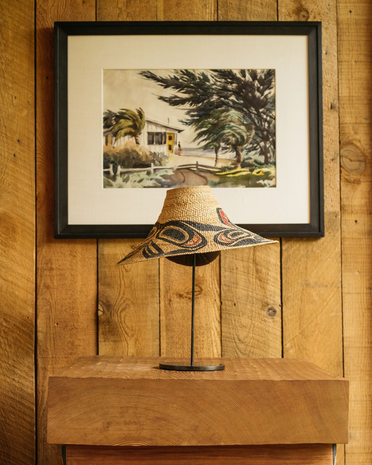 A desk with a hat stand and hat.  A framed work of art hangs over the desk.  The wall is made of wood.