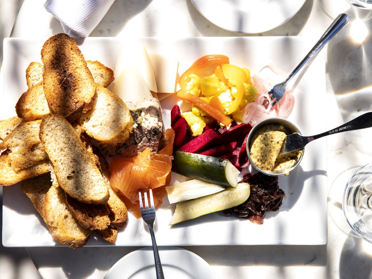 A charcuterie plate with pate, sliced fish, pickled vegetables, toasted bread, mustard, and other fixings