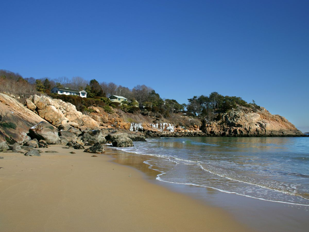 A sandy beach, body of water, and a hillside with trees, rocks, and houses.