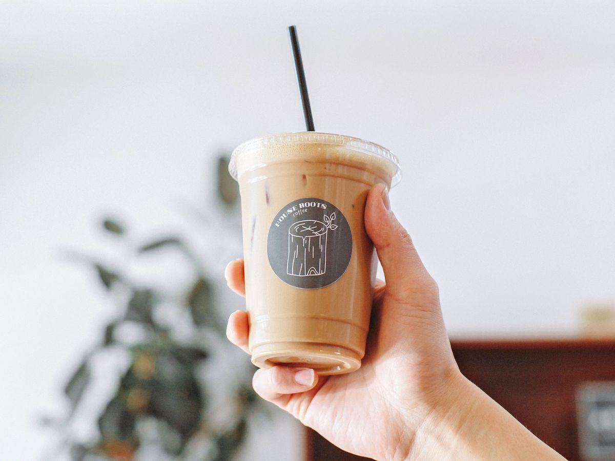 A hand in sunlight holds up a plastic clear cup of latte with black straw.
