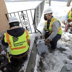 Dominion Energy utility workers Kylie Hrubes, left, Ramone Barrera and Joey Stephenson replace a gas meter in West Valley City on Wednesday, Feb. 17, 2021.