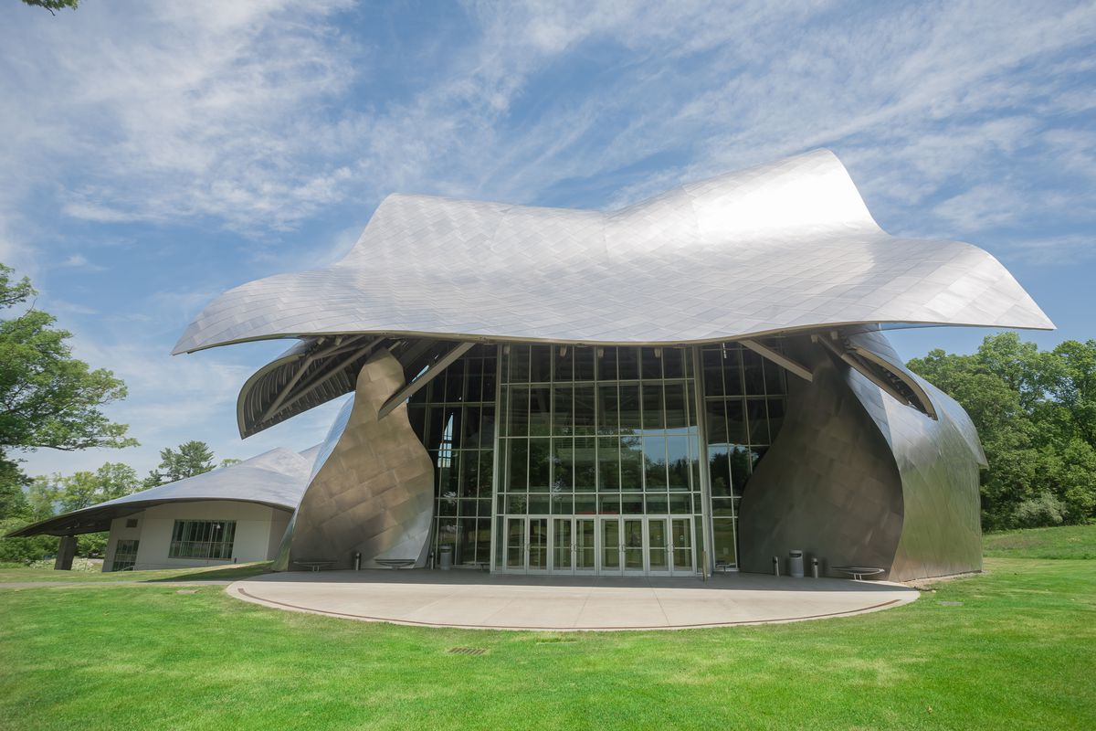 The performing arts building at Bard College, the Fisher Center, designed by Frank Gehry. The roof and walls are curved metal. There is a glass entryway. The building is surrounded by a green grass lawn.
