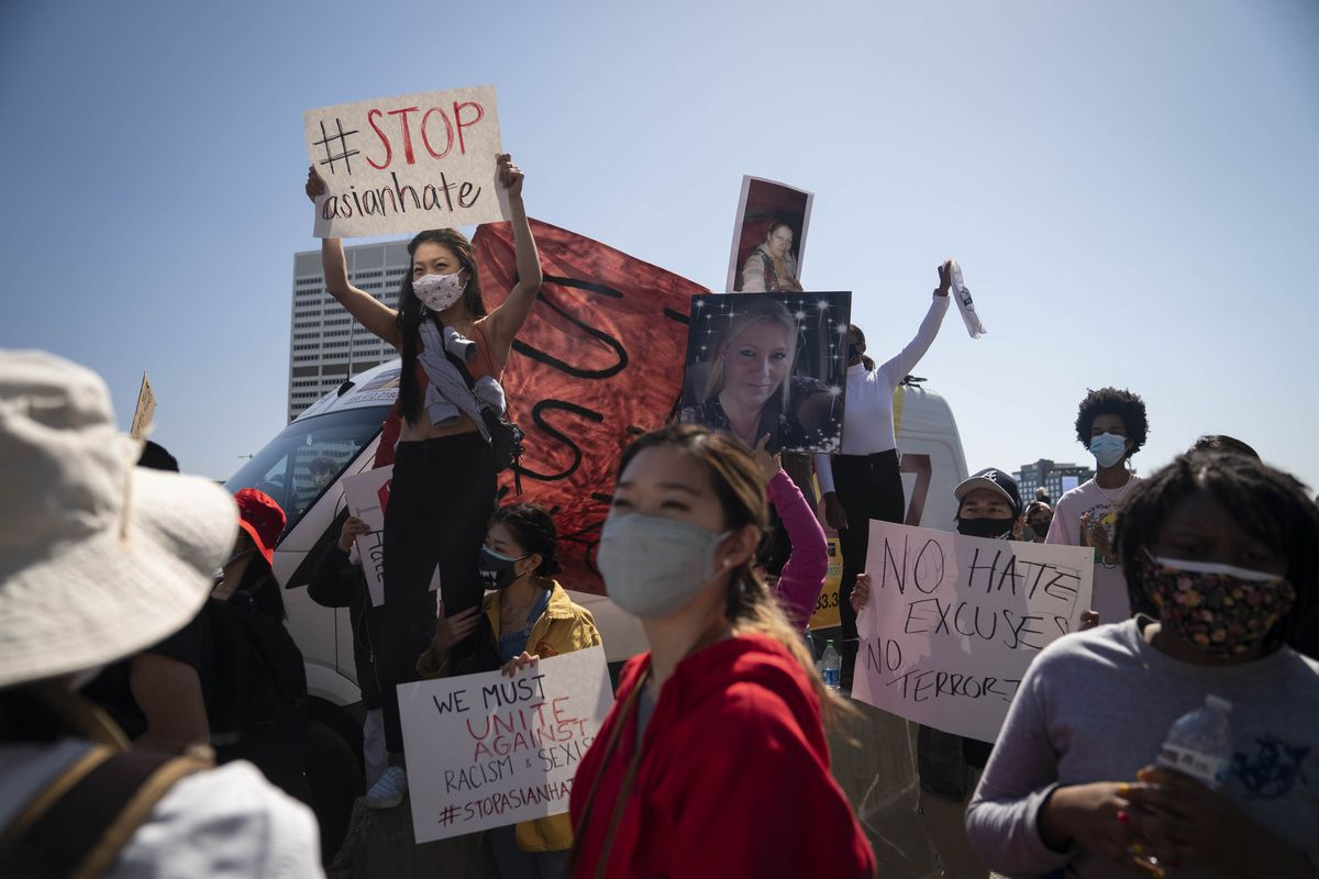 """A crowd of masked people — mostly Asian and Black — carry signs under a blue sky. One sign reads, """"No Hate, No Excuses;"""" another says, """"We must unite against racism & sexism #stopasianhate."""" One woman holds up a large photo of shooting victim Delaina Ashley Yaun Gonzalez. In the center of the crowd, an Asian woman stands on a concrete barrier, and raises a sign reading, in bold red and black letters, """"#STOPasianhate."""""""