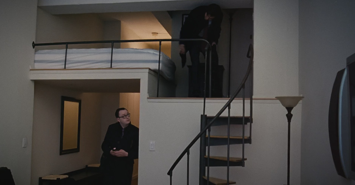 A tall man crouches under a low ceiling on a loft level of an apartment in the HBO show Succession. Another man stands at the foot of the staircase leading up to the loft.