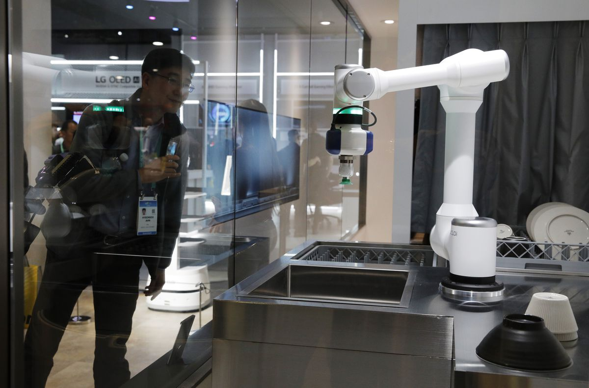 An attendee looks at an LG CLOi CoBot configured to wash dishes in a mock restaurant setting at the LG booth during the CES tech show in Las Vegas.