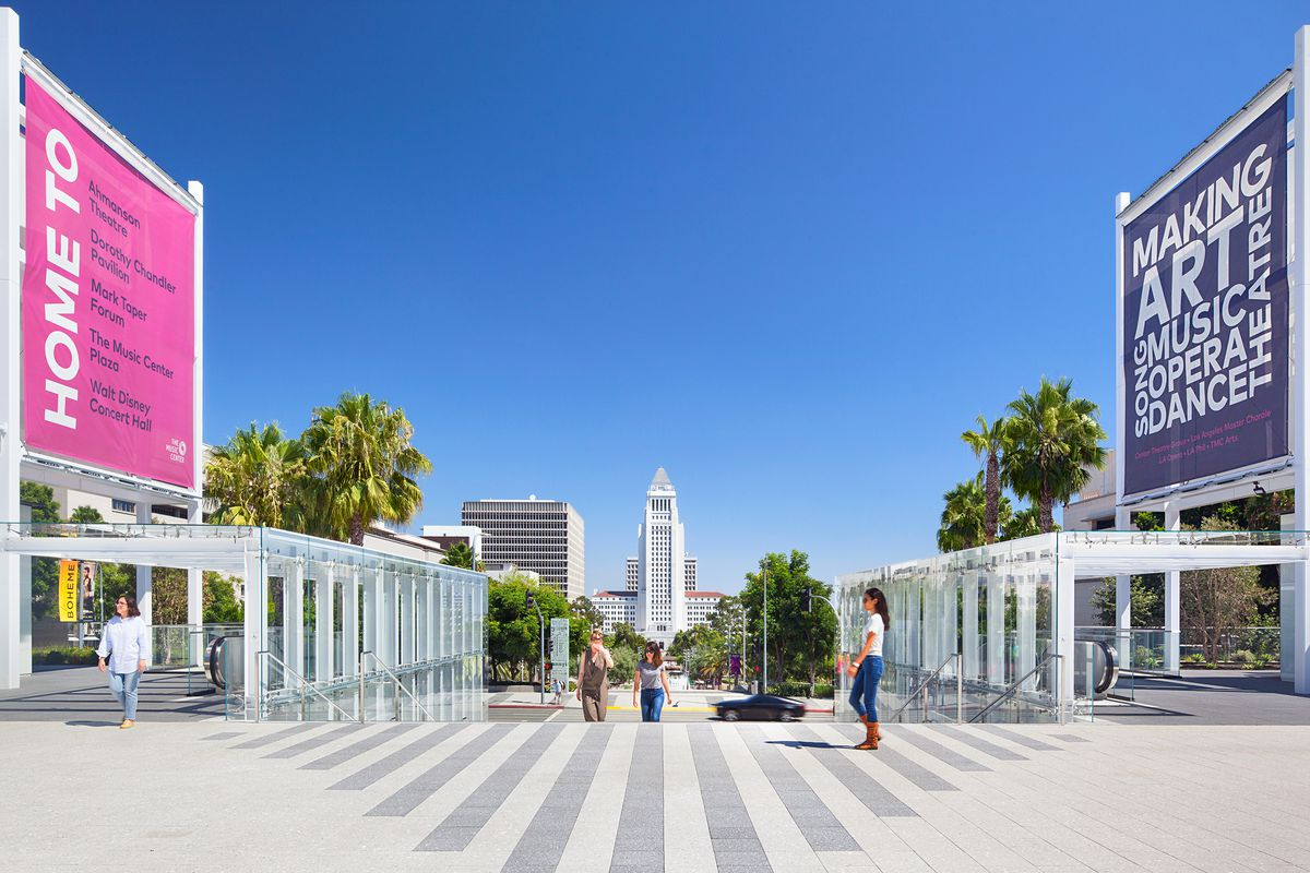 A large, open area with two escalators on either side. The escalators are covered by glass structures. In the background, LA City Hall is visible.