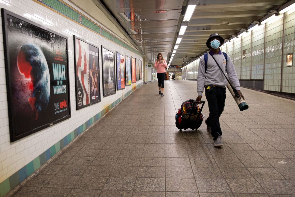 Commuters walk through the Times Square subway station while officials encourage people to work from home during the coronavirus scare.