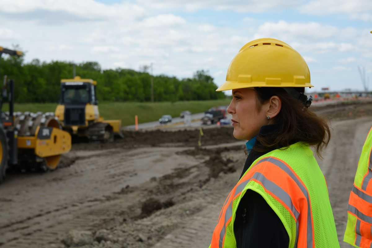 Gov. Whitmer in hard hat and vest with construction machinery in background at road building site