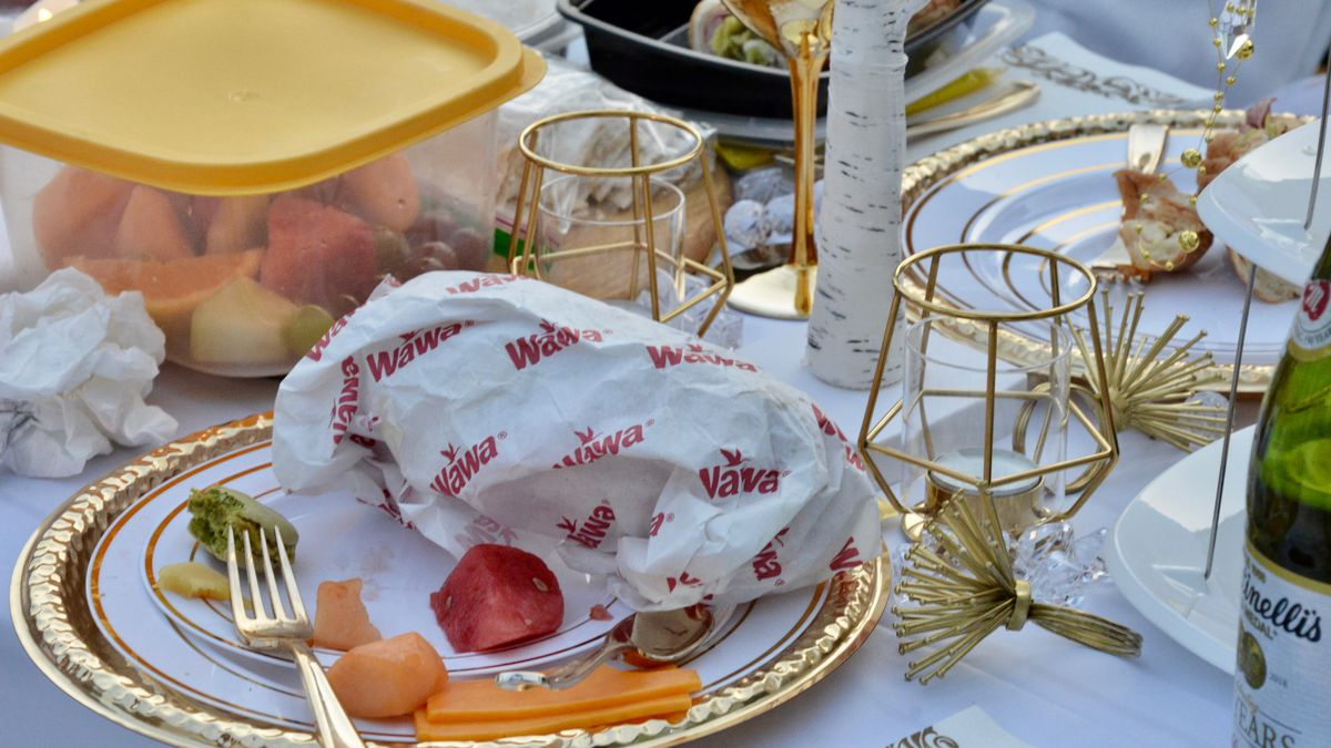 a table with container of fruit and plate with Wawa sandwich wrapper