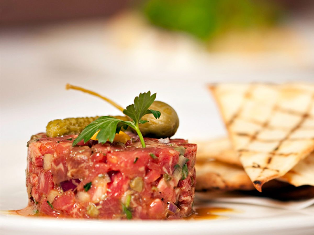 Steak tartare topped with a cornichon at Mooo, served with a side of grilled bread