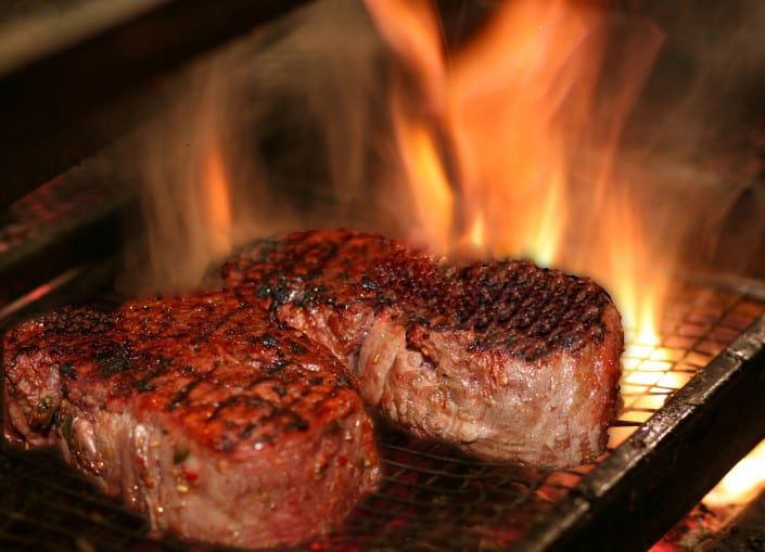 Two steaks cooking over an open fire.